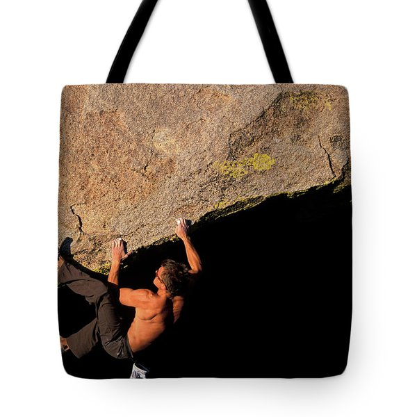 A Male Rock Climber Crimps While Tote Bag