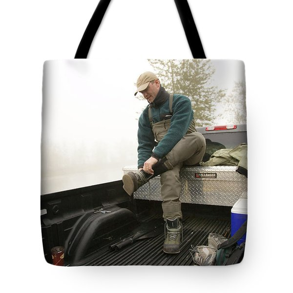 A Man Puts On Hip Waders To Fly-fish Tote Bag