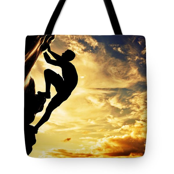A Silhouette Of Man Free Climbing On Rock Mountain At Sunset Tote Bag by Michal Bednarek