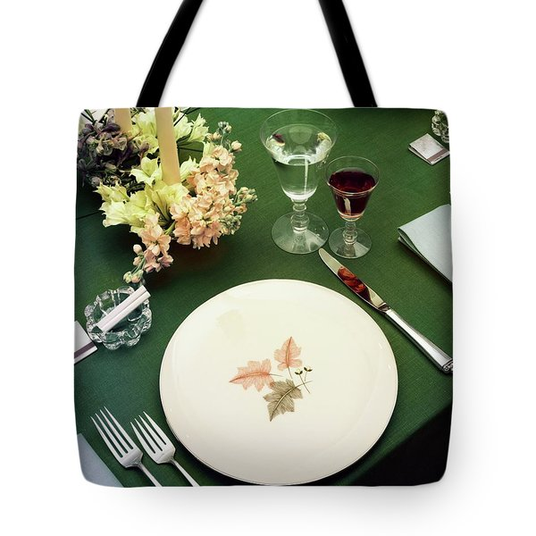 A Table Setting On A Green Tablecloth Tote Bag