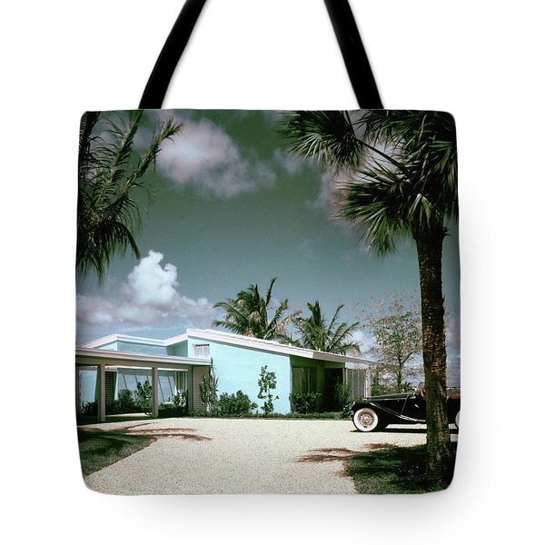 A Vintage Car Parked Outside A Blue House Tote Bag