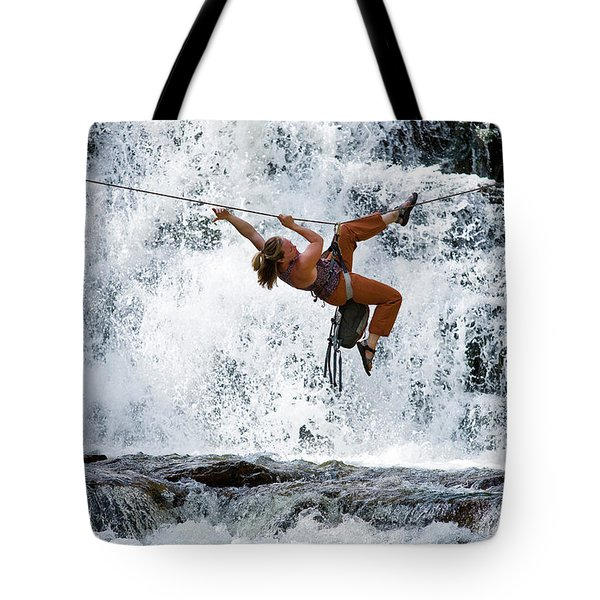 A Woman Crosses A Waterfall Using Tote Bag