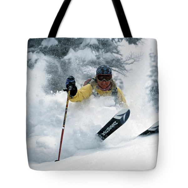 A Woman Teleskiing On A Powder Day Tote Bag