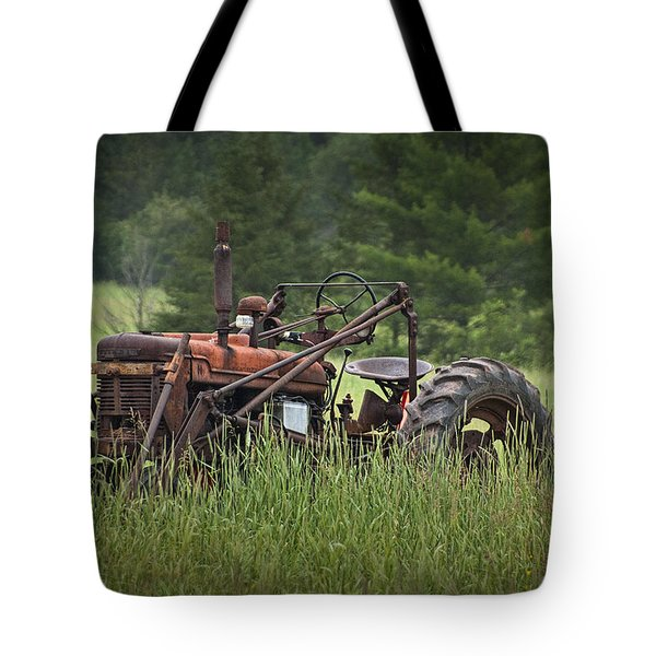 Abandoned Farm Tractor In The Grass Tote Bag by Randall Nyhof