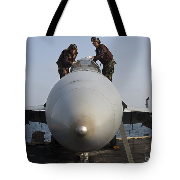Airmen Clean The Canopy Of An Fa-18f Tote Bag by Stocktrek Images