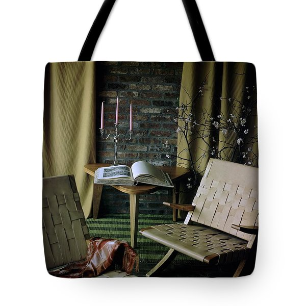 An Armchair Beside A Table And An Old Book Tote Bag