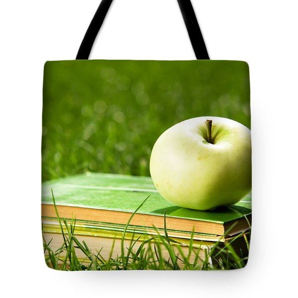 Apple On Pile Of Books On Grass Tote Bag by Michal Bednarek
