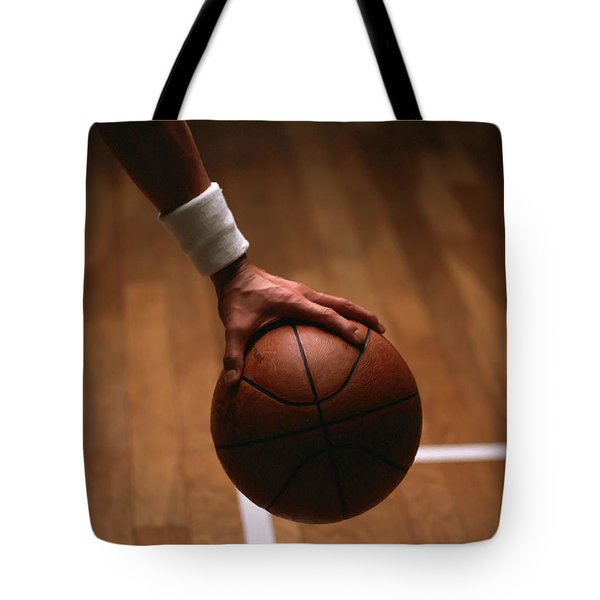 Basketball Ball In Male Hands Tote Bag by Lanjee Chee
