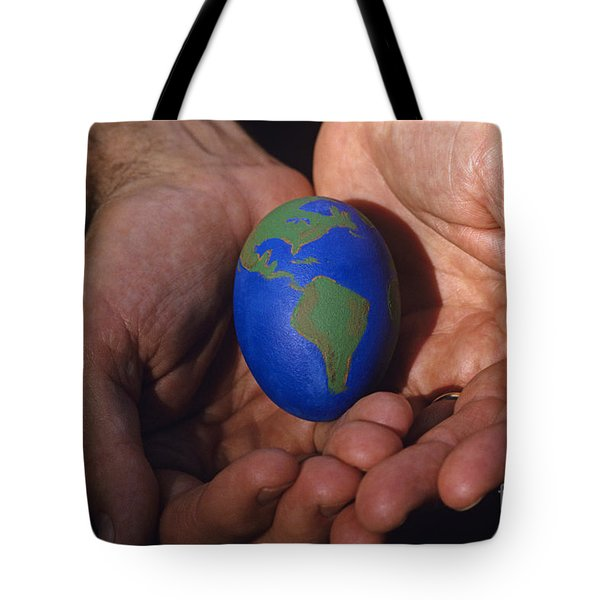 Man Holding Earth Egg Tote Bag by Jim Corwin