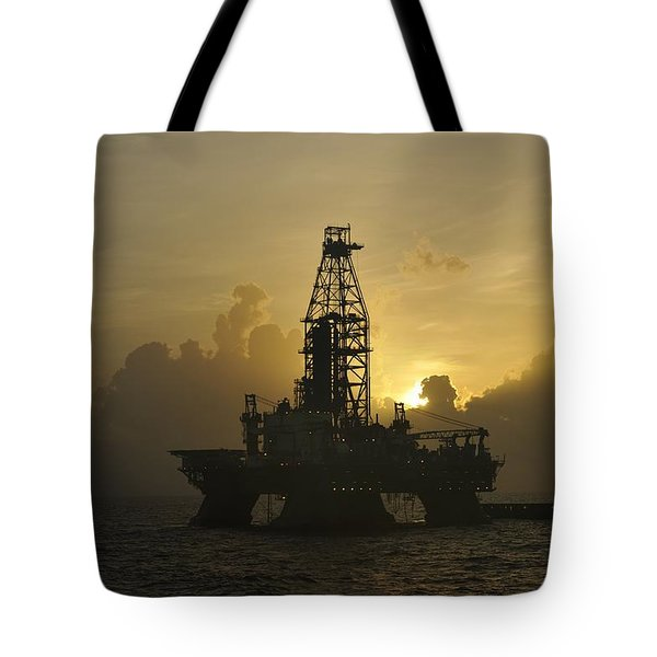 Tote Bag featuring the photograph Offshore Oil Rig With Sun And Clouds by Bradford Martin