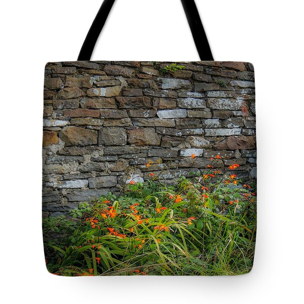 Orange Wildflowers Against Stone Wall Tote Bag