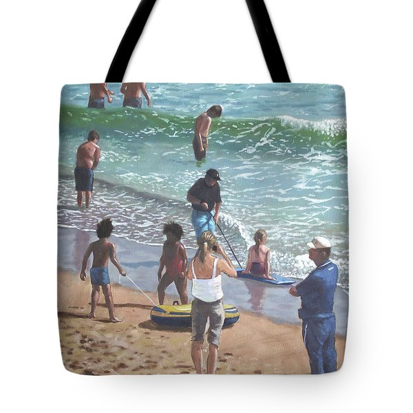 people on Bournemouth beach pulling dingys Tote Bag