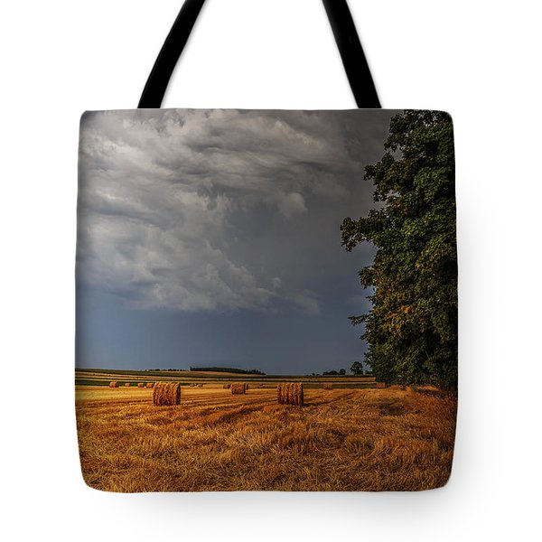 Tote Bag featuring the photograph Storm Clouds Over Harvested Field In Poland by Julis Simo