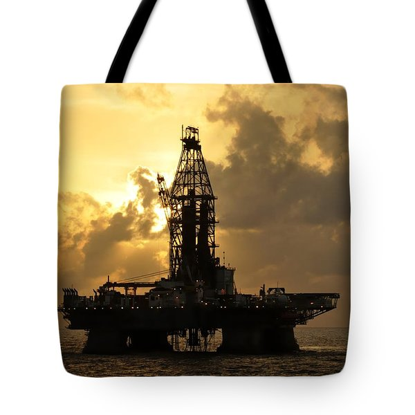 Tote Bag featuring the photograph Sun Behind Oil Rig With Clouds by Bradford Martin