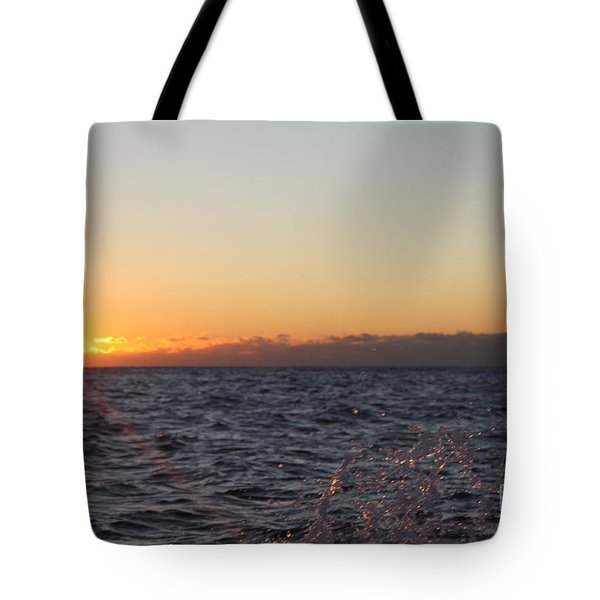 Sun Rising Through Clouds In Rough Waters Tote Bag by John Telfer