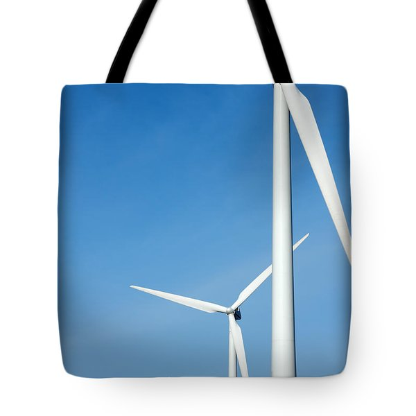 Three Mighty Windmills In A Row Against A Blue Sky. Tote Bag