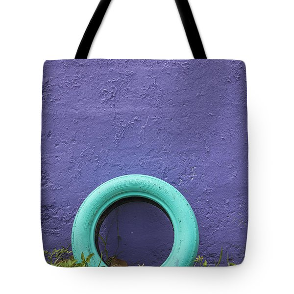 Tote Bag featuring the photograph Tire Painted In Bright Color Leaning Against Wall In San Juan Pue by Bryan Mullennix