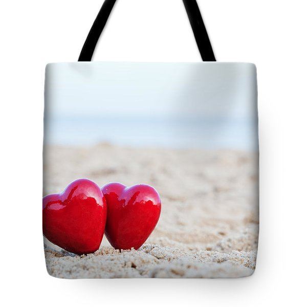 Two Red Hearts On The Beach Symbolizing Love Tote Bag by Michal Bednarek