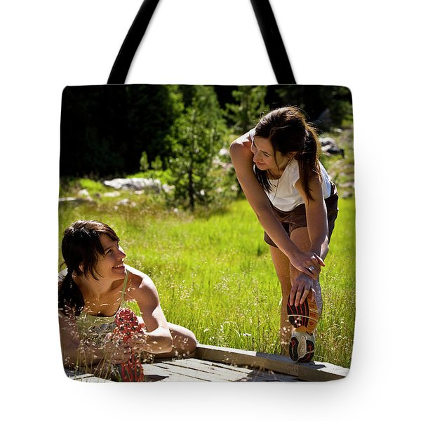Two Women Stretch Prior To Running Tote Bag