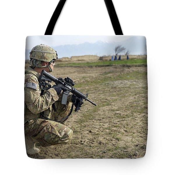 U.s. Soldier Patrols A Village Tote Bag by Stocktrek Images