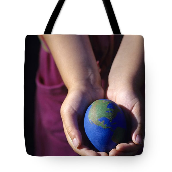 Young Girl Holding Earth Egg Tote Bag by Jim Corwin