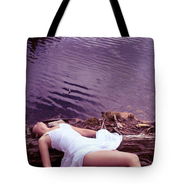 Young Woman In White Dress Lying Near Lake Tote Bag