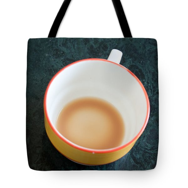 Tote Bag featuring the photograph A Cup With The Remains Of Tea On A Green Table by Ashish Agarwal