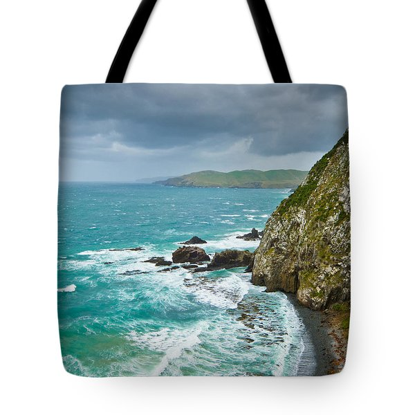 Cliffs Under Thunder Clouds And Turquoise Ocean Tote Bag by Ulrich Schade