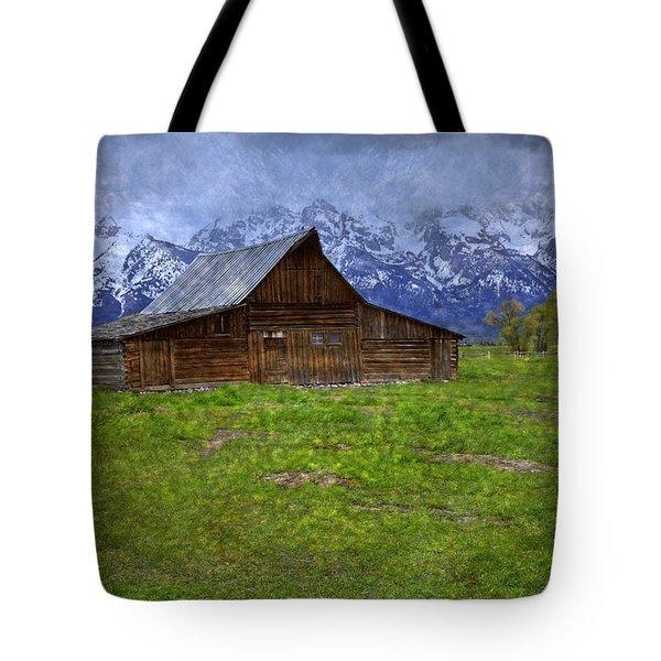 Grand Teton Iconic Mormon Barn Spring Storm Clouds Tote Bag by John Stephens