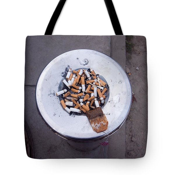 Tote Bag featuring the photograph A Lot Of Cigarettes Stubbed Out At A Garbage Bin by Ashish Agarwal