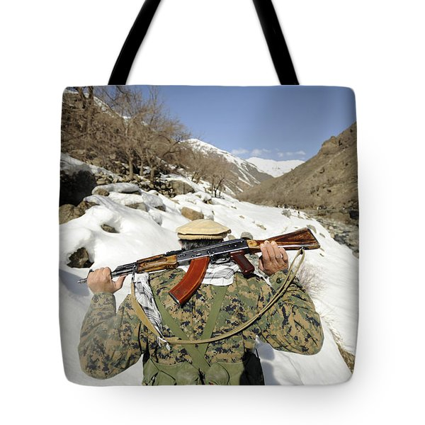 A Mujahadeen Guard Walks With U.s Tote Bag by Stocktrek Images