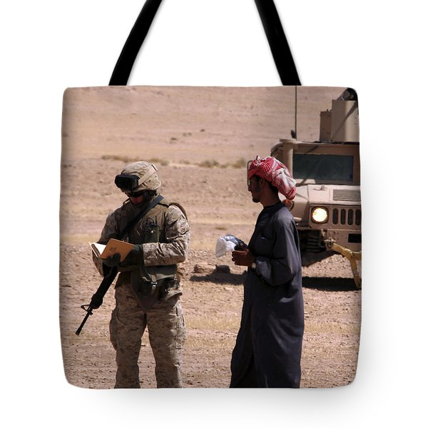 A Soldier Communicates With A Local Tote Bag by Stocktrek Images