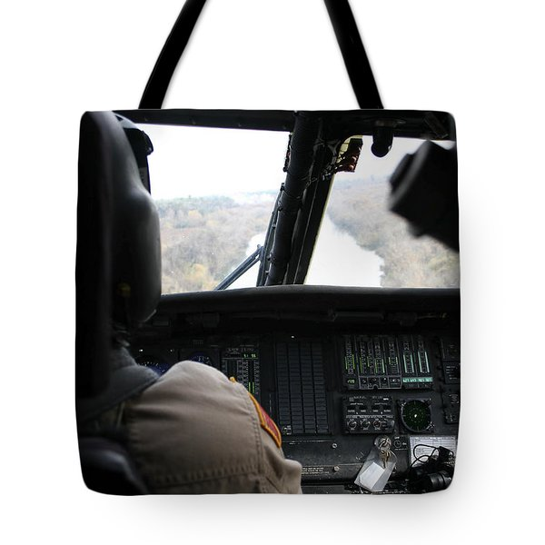 A Uh-60 Blackhawk Flies The River To An Tote Bag by Terry Moore