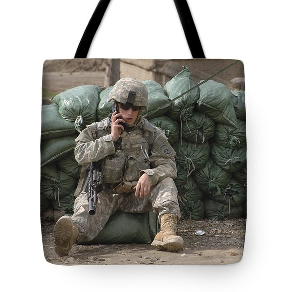 A U.s. Army Soldier Talks On A Radio Tote Bag by Stocktrek Images
