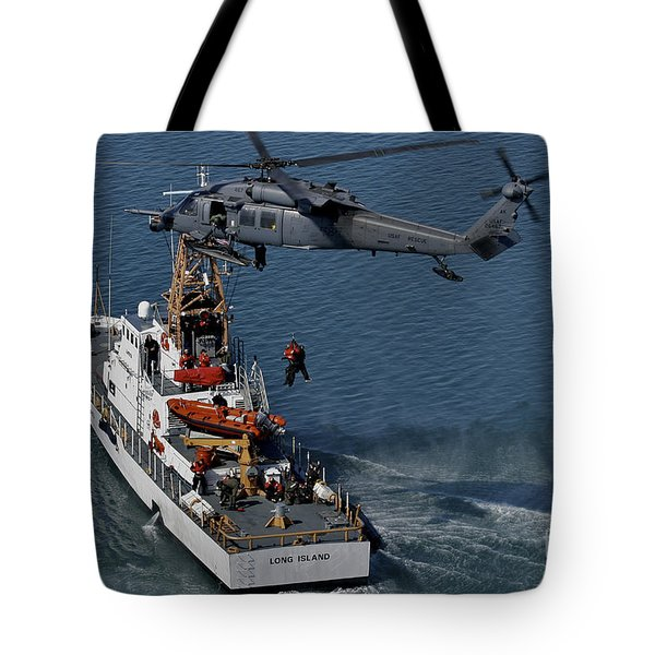 An Hh-60g Pave Hawk Performs A Hoist Tote Bag by Stocktrek Images