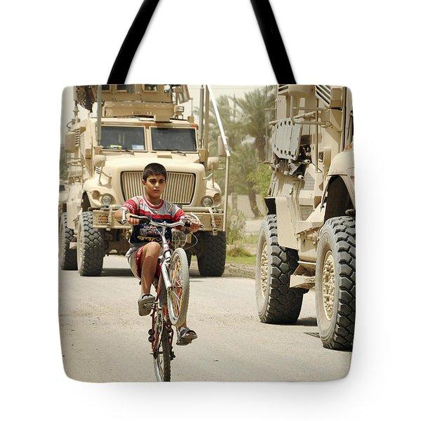 An Iraqi Boy Rides His Bike Past A U.s Tote Bag by Stocktrek Images