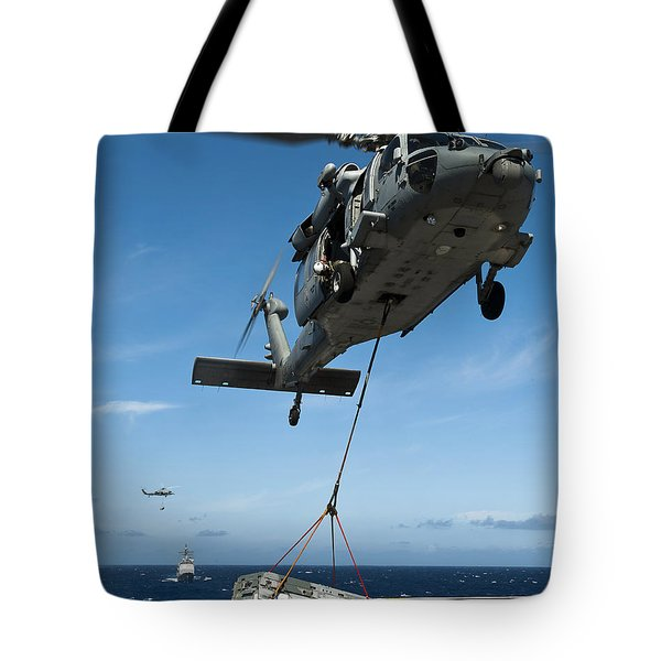 An Mh-60s Sea Hawk Helicopter Lowers Tote Bag by Stocktrek Images