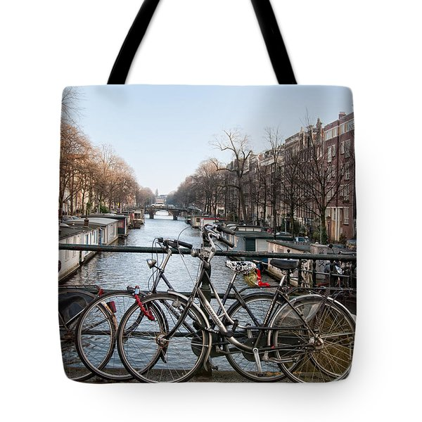 Tote Bag featuring the digital art Bikes On The Canal In Amsterdam by Carol Ailles