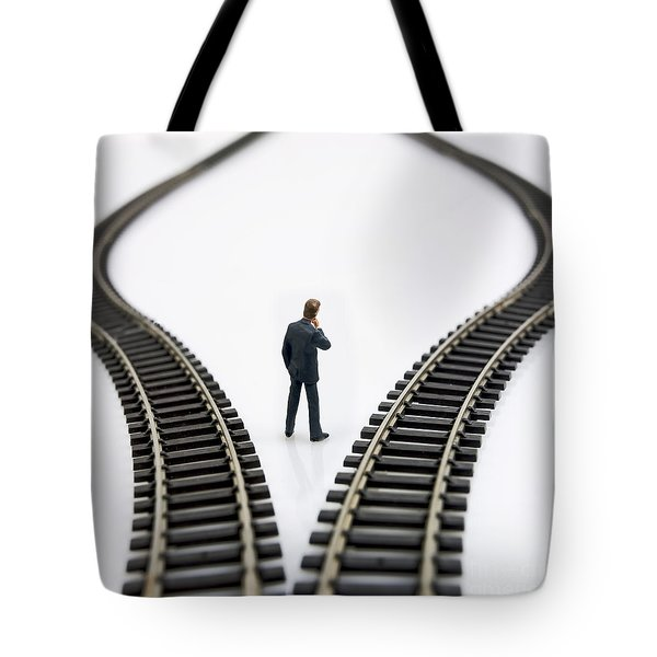 Figurine Between Two Tracks Leading Into Different Directions  Symbolic Image For Making Decisions Tote Bag