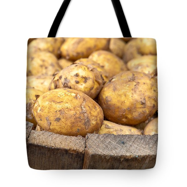 Freshly Harvested Potatoes In A Wooden Bucket Tote Bag by Tom Gowanlock