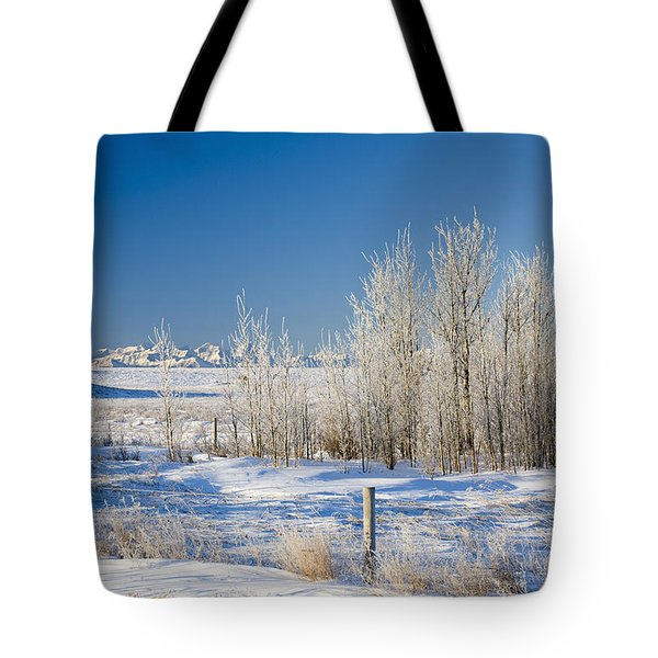 Frost-covered Trees In Snowy Field Tote Bag by Michael Interisano