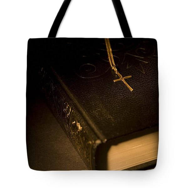 Gold Cross Pendant Resting On A Book Tote Bag by Philippe Widling