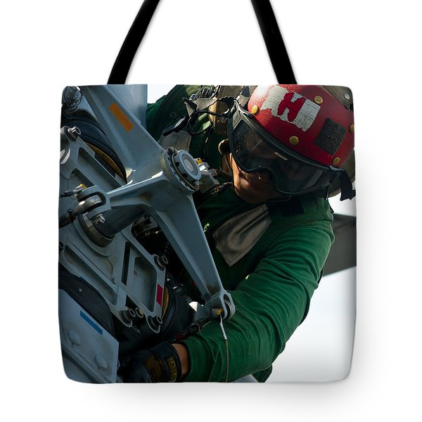 Mechanic Inspects An Mh-60r Sea Hawk Tote Bag by Stocktrek Images