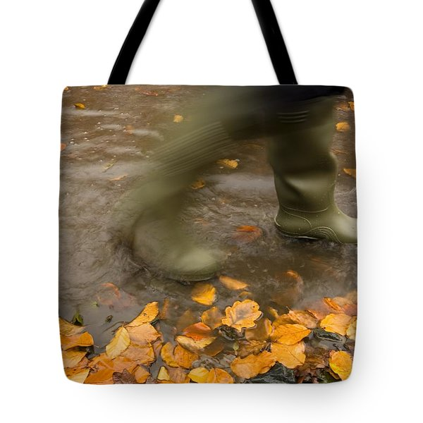 Person In Motion Walks Through Puddle Tote Bag by John Short