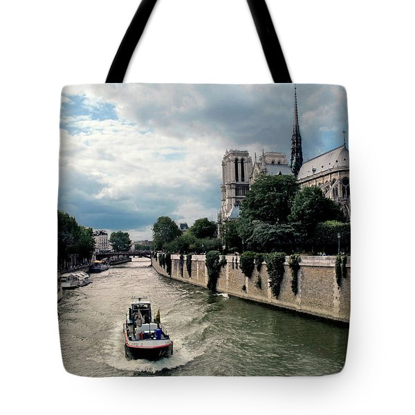 Tote Bag featuring the photograph Tour Boat Passing Notre Dame by Dave Mills