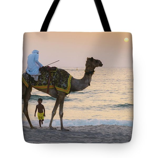Little Boy Stares In Amazement At A Camel Riding On Marina Beach In Dubai, United Arab Emirates -  Tote Bag