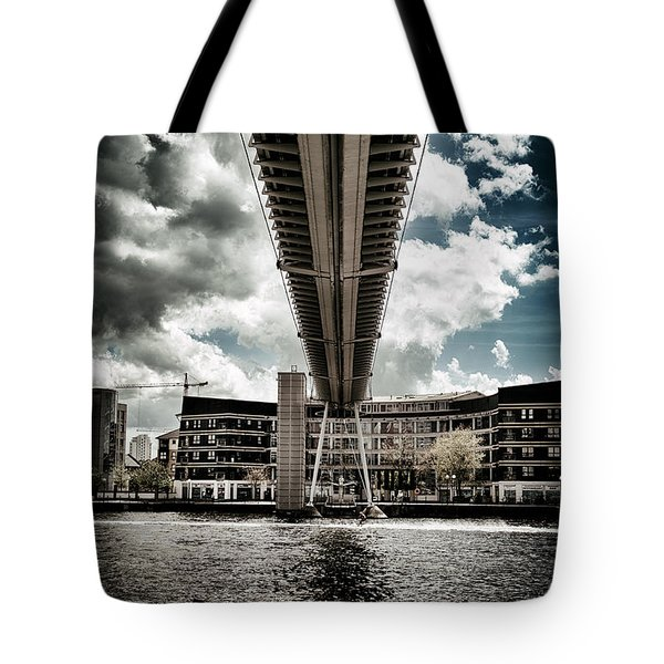 Tote Bag featuring the photograph A Water Skier Speeds Past The Royal Victoria Dock Bridge by Lenny Carter
