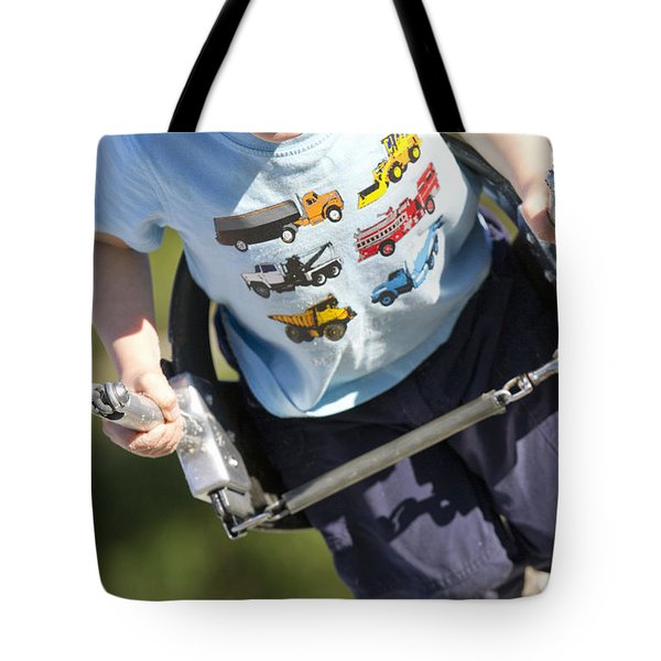 Young Boy Smiling Swinging In A Swing Tote Bag by Robert Postma
