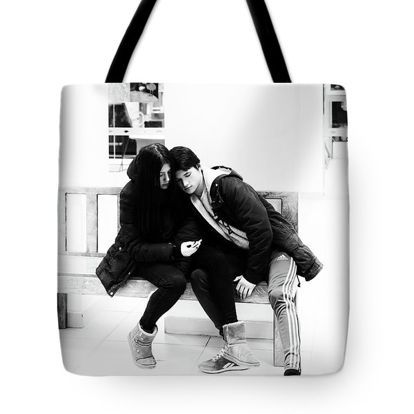 Tote Bag featuring the photograph Young Romantic Couple Sharing A Mobile Phone by John Williams