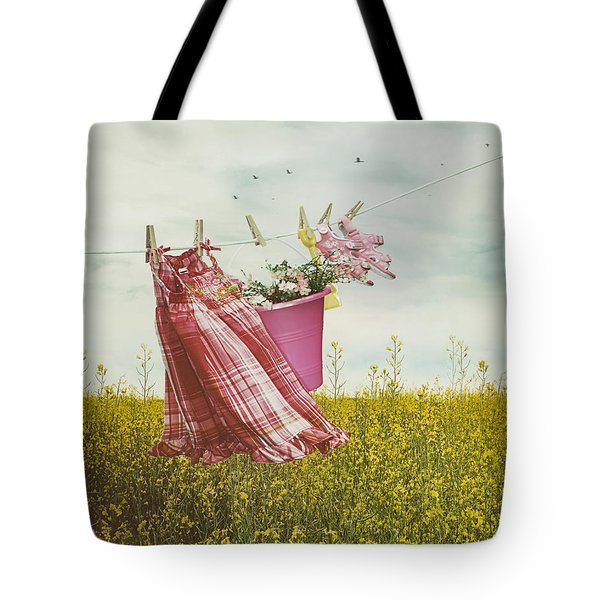 Child's Dress And Toys Hanging On Line With Farmhouse In Backgro Tote Bag by Sandra Cunningham